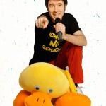 Ganzkörperfoto von Klaus Foitzik, wie er hinter einer großen gelben Plüschente kauert und in der einen Hand ein Mikrofon hält  und mit der anderen auf den Betrachter deutet