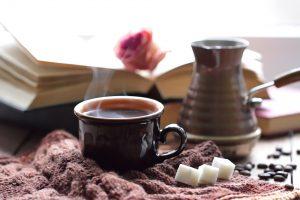 Foto eines Herbststillebens: Tasse Kaffee, Würfelzucker, Strickschal, Buch und Rose